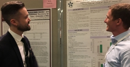 Two people talking about a research poster